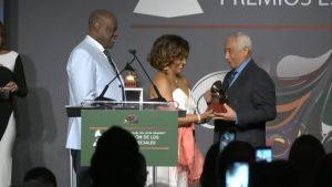 Rafael Solano mientras recibe de manos de los populares artistas Milly Quezada y Johnny Ventura,  el galardón otorgado por la Academia Latina de la Grabación.